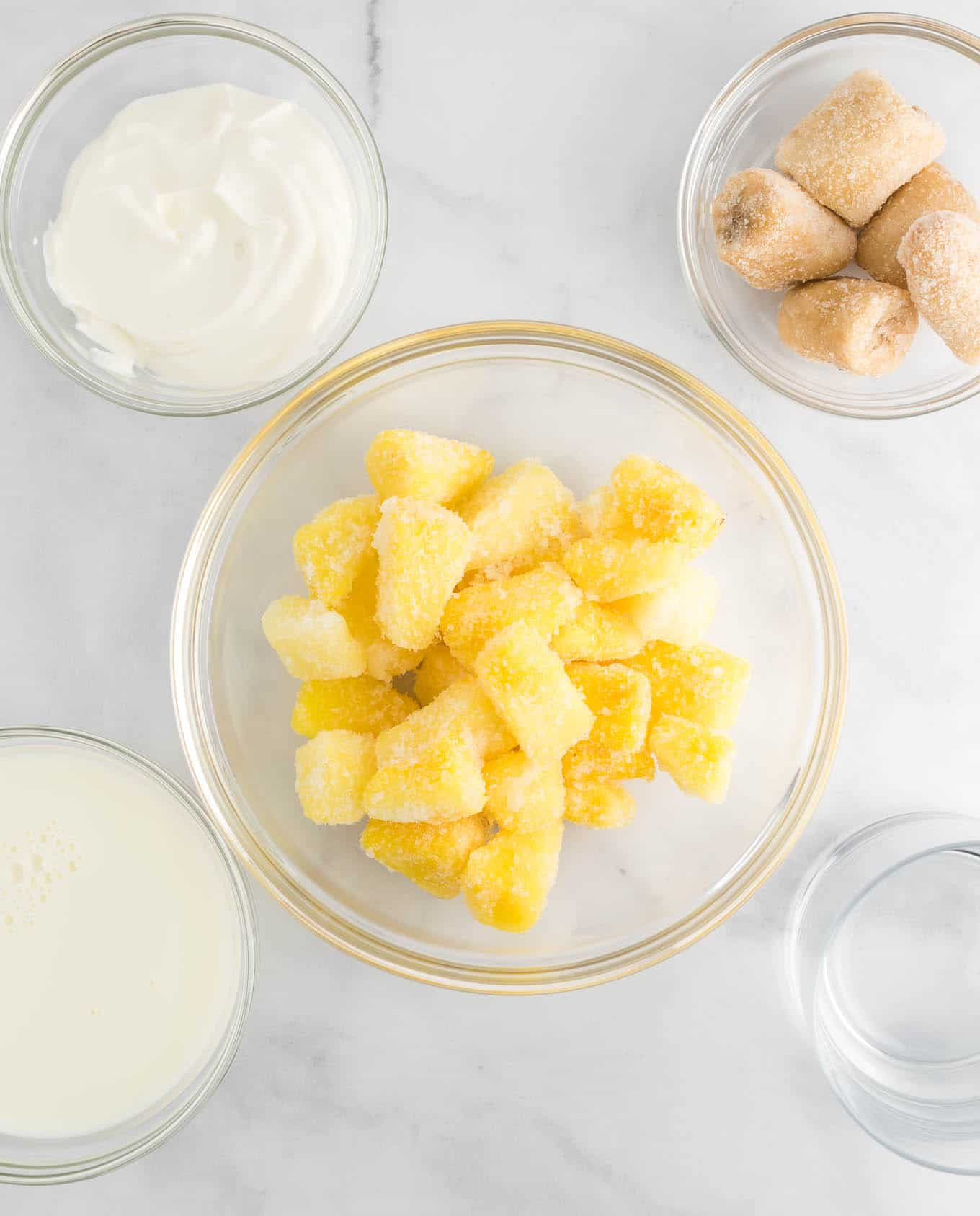 the ingredients in clear bowls - frozen pineapple chunks, greek yogurt, frozen banana chunks, and milk