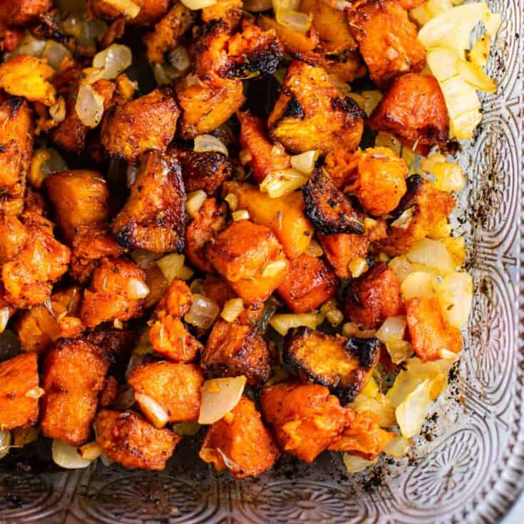 sweet potatoes diced up with onion in a glass baking dish