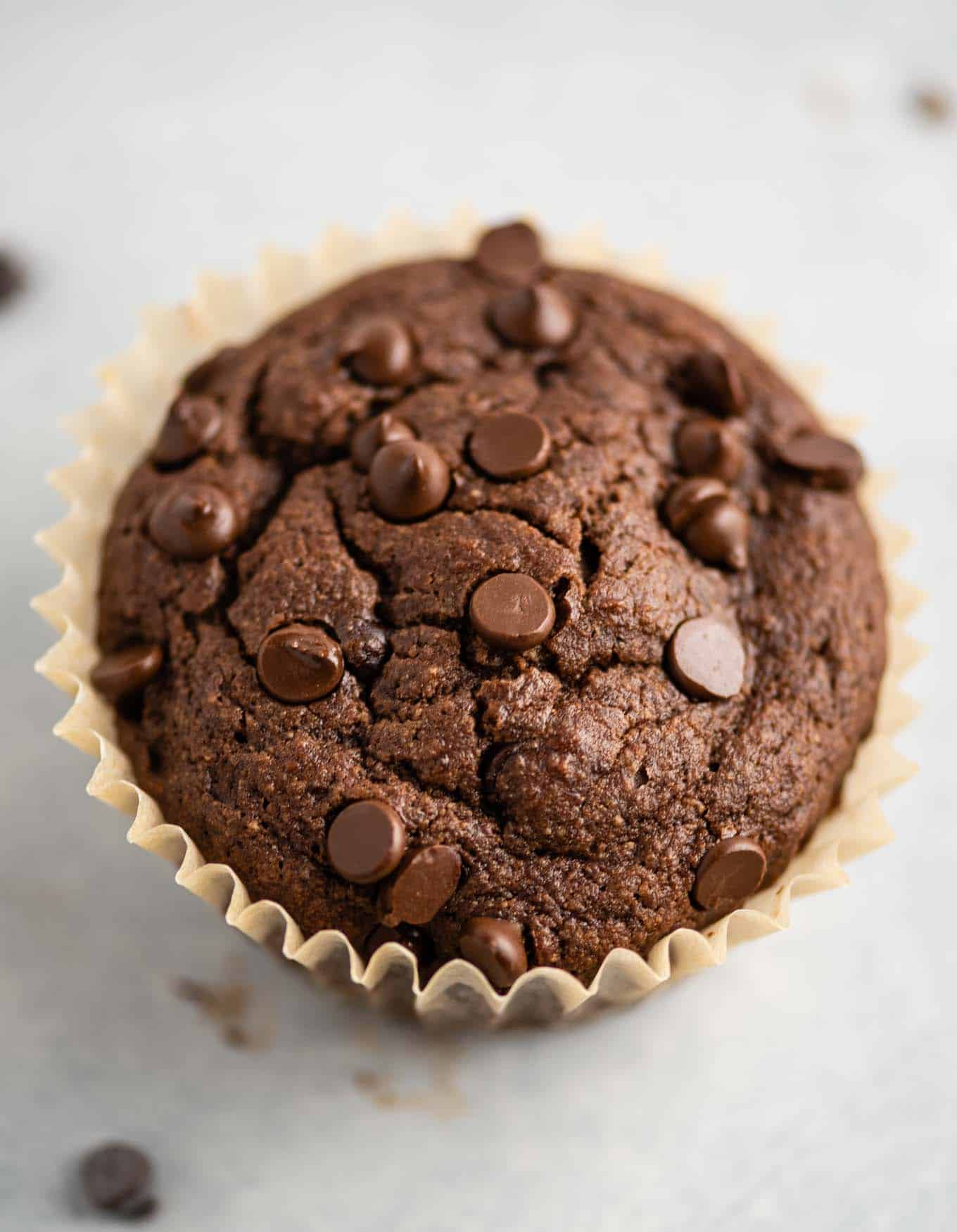 single gluten free chocolate muffin in a parchment paper muffin liner