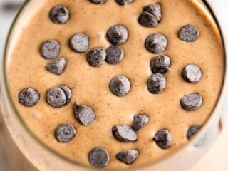 chocolate peanut butter banana smoothie in a glass sprinkled with mini chocolate chips