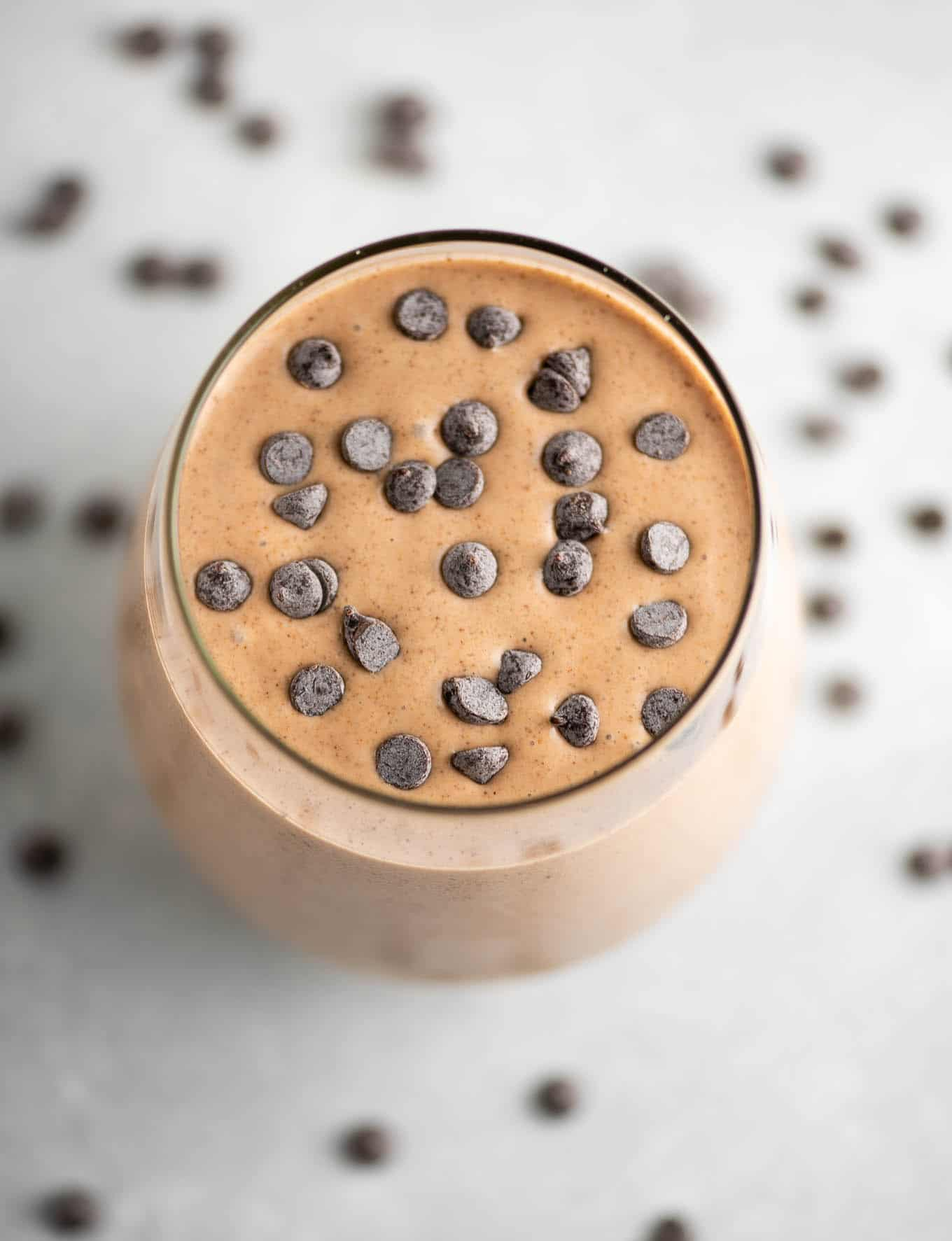 chocolate smoothie in a glass topped with mini chocolate chips