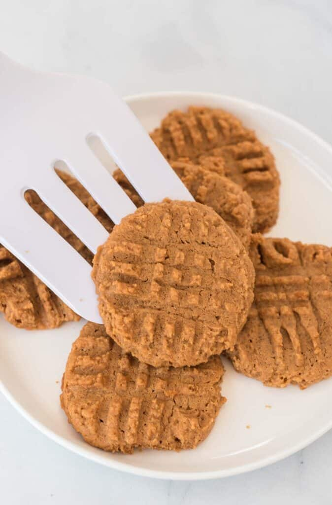 a spatula placing a peanut butter cookie onto a plate