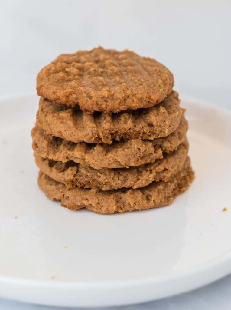 five peanut butter cookies stacked on a plate