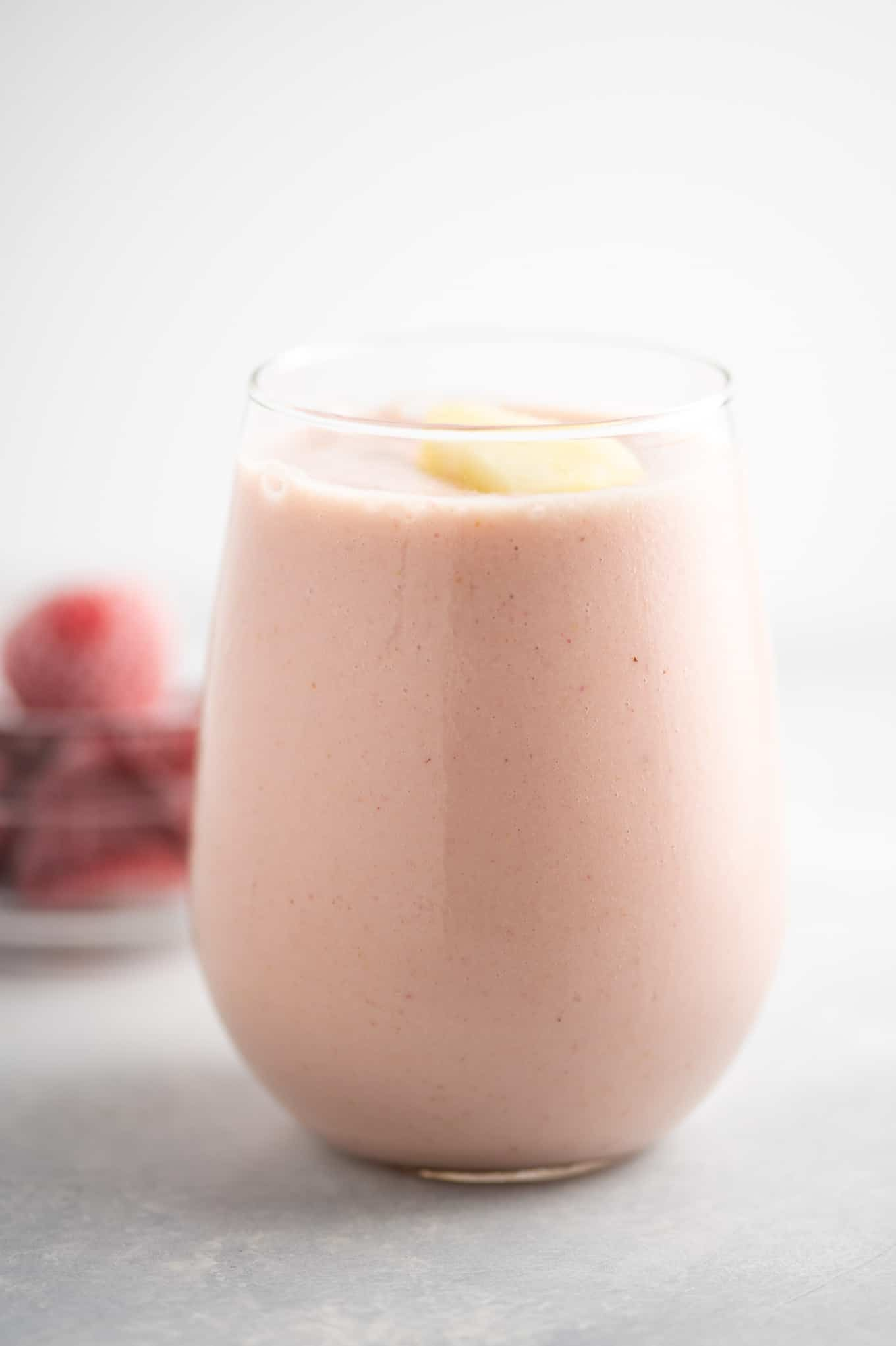 pineapple strawberry smoothie in a glass with frozen strawberries in the background