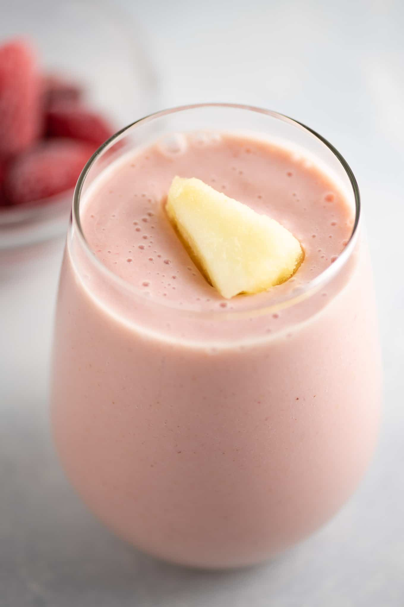 strawberry and pineapple smoothie with frozen pineapple on top