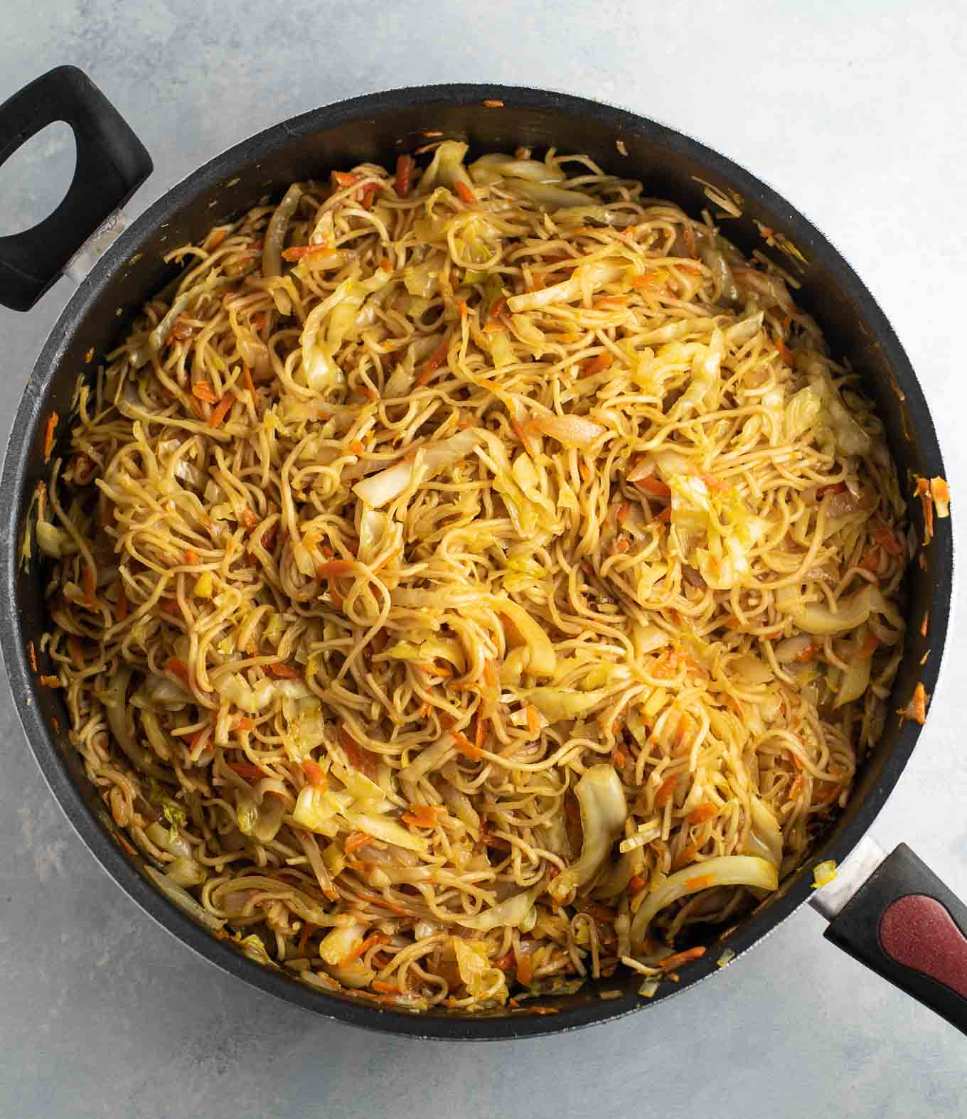 overhead view of a skillet full of cooked cabbage stir fry noodles