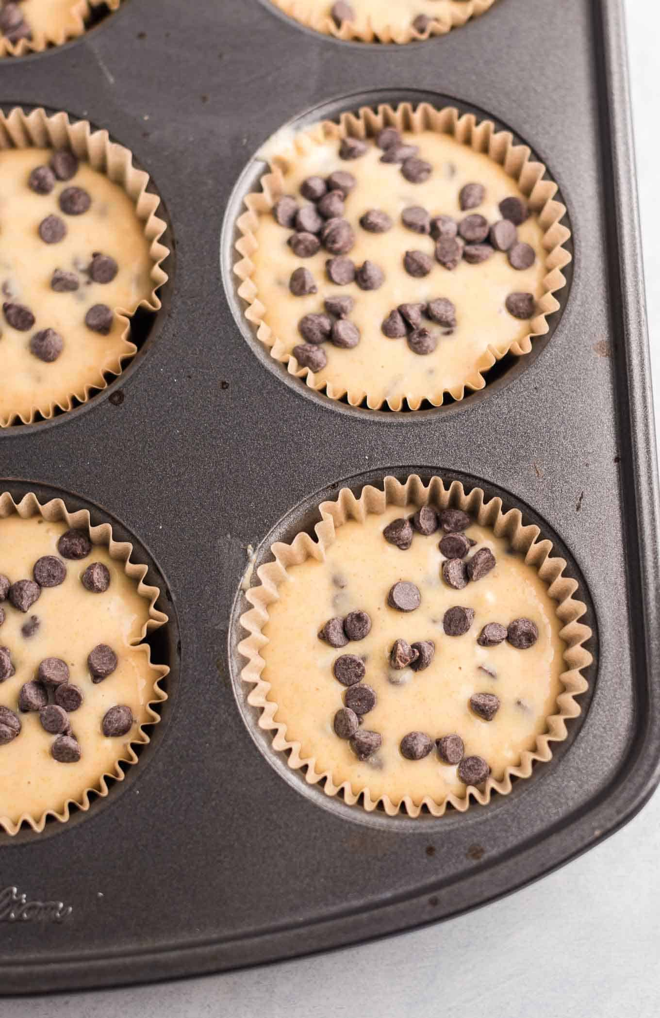 muffin batter in the muffin tins topped with extra mini chocolate chips