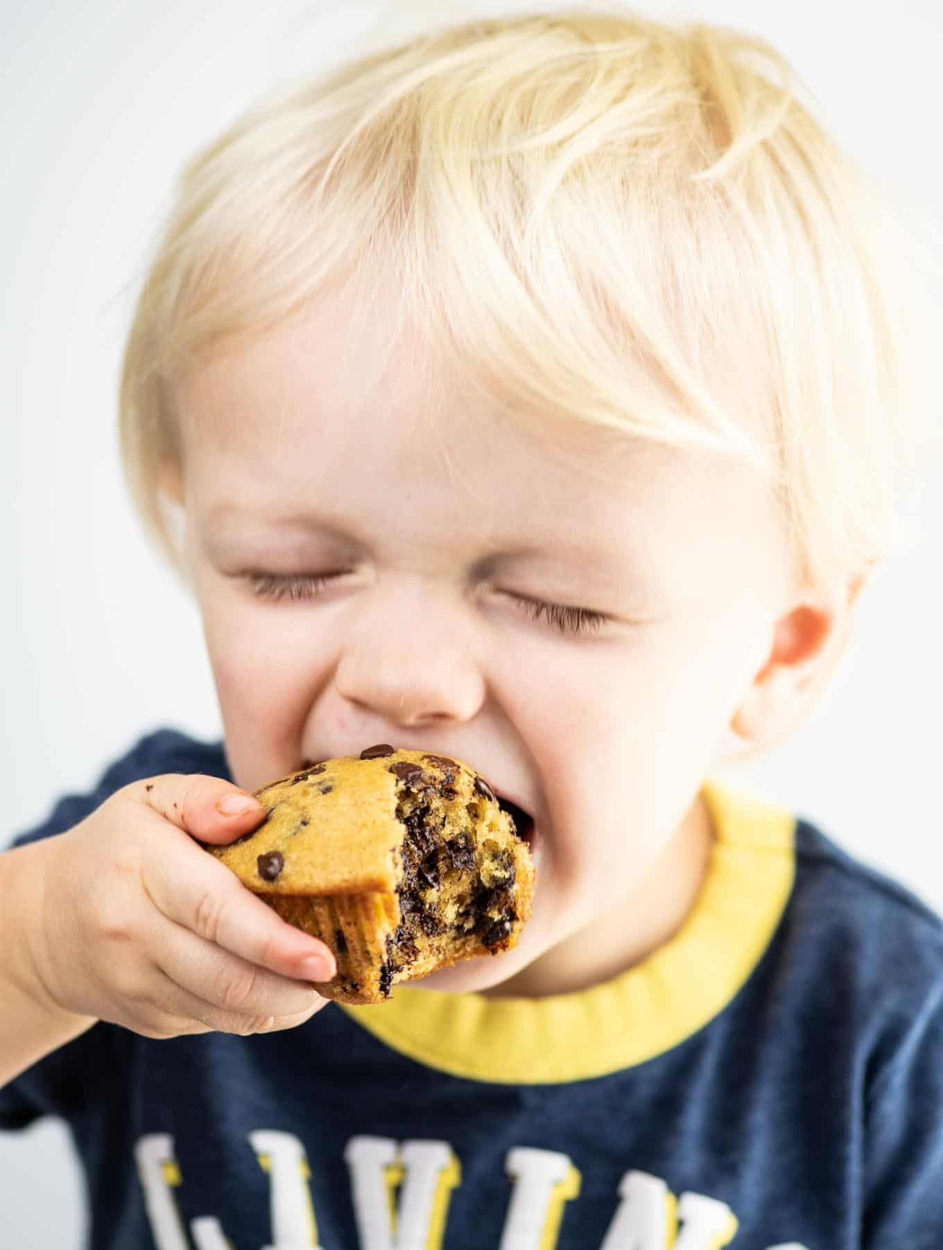 toddler taking a bite of a chocolate chip muffin