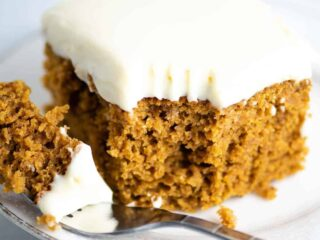 pumpkin cake recipe with cream cheese frosting slice with a bite taken out on a fork