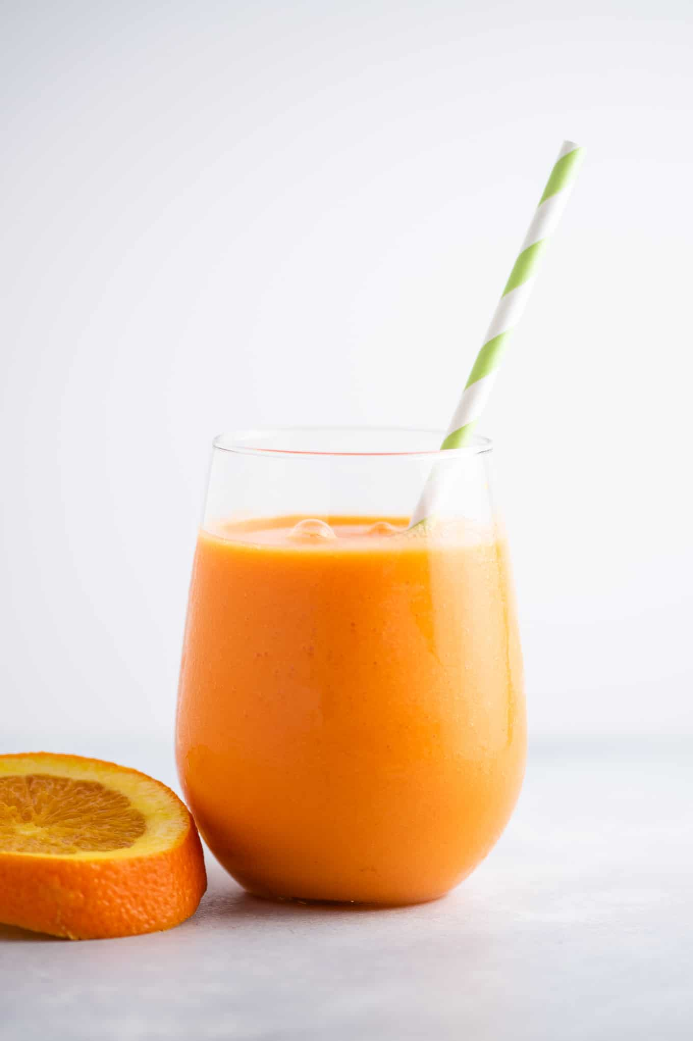 carrot orange smoothie with a green and white straw in it