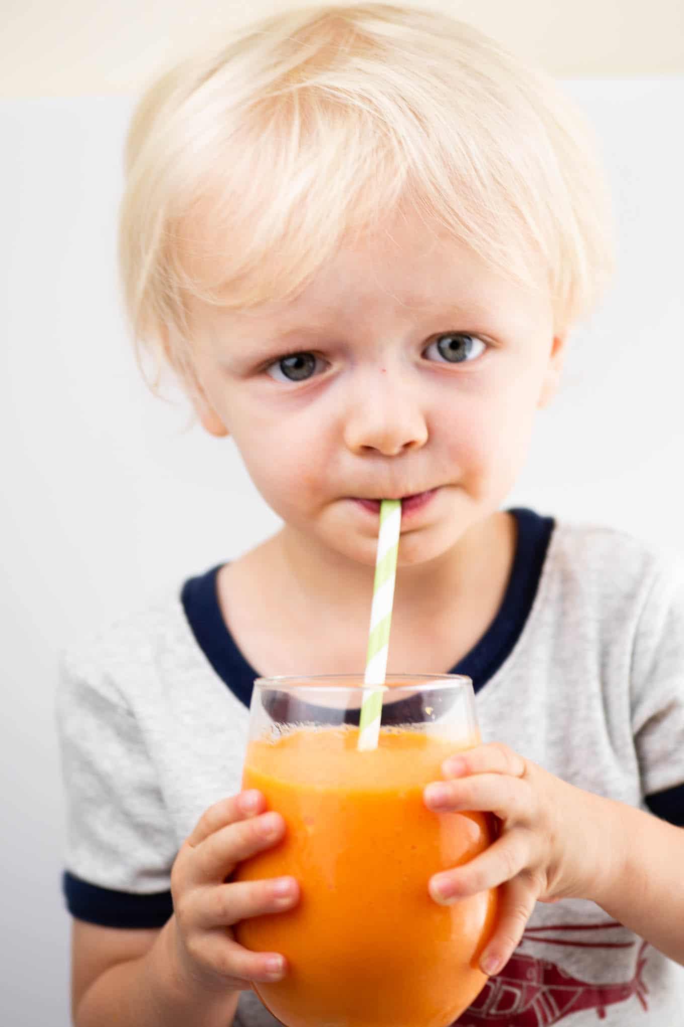 toddler drinking an orange smoothie