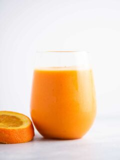 orange smoothie in a glass with a slice of orange sitting beside it