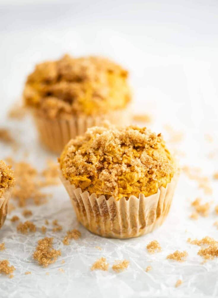 pumpkin cake mix muffins on wax paper with brown sugar sprinkled around