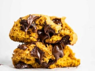 pumpkin chocolate chip cookies stacked with melted chocolate chips inside