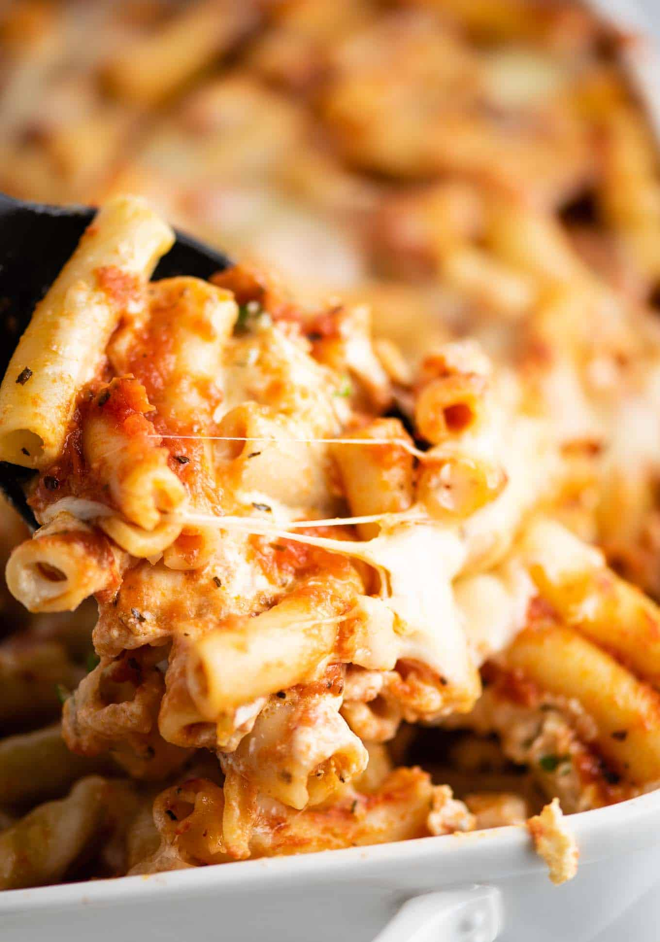 scoop of ziti coming out of the dish