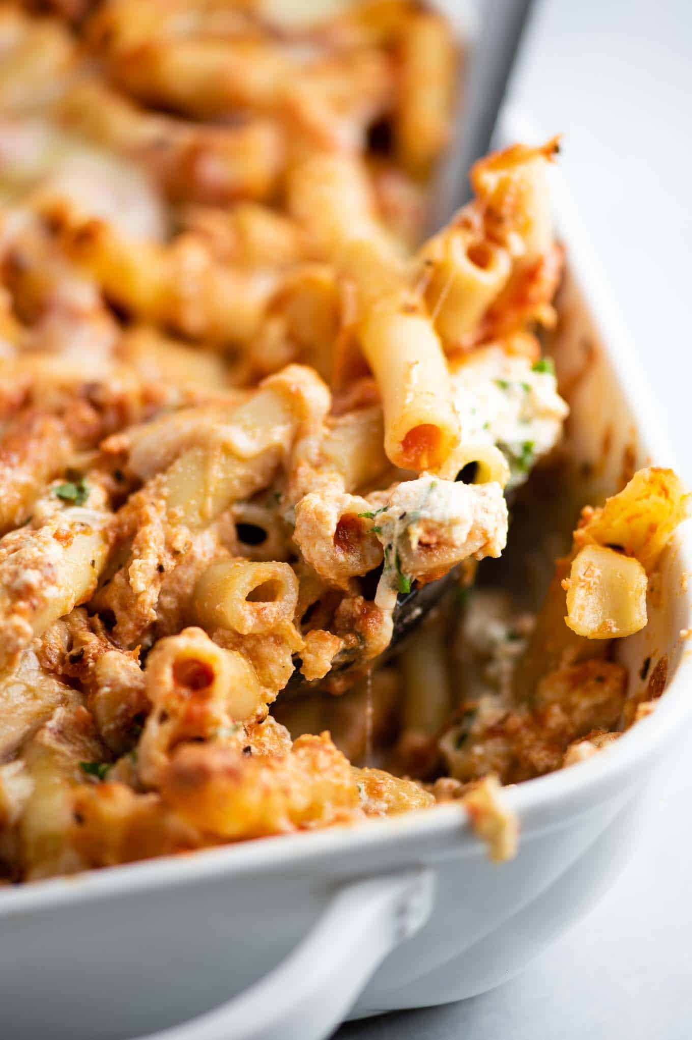 a spoon dishing out a scoop of ziti from the pan