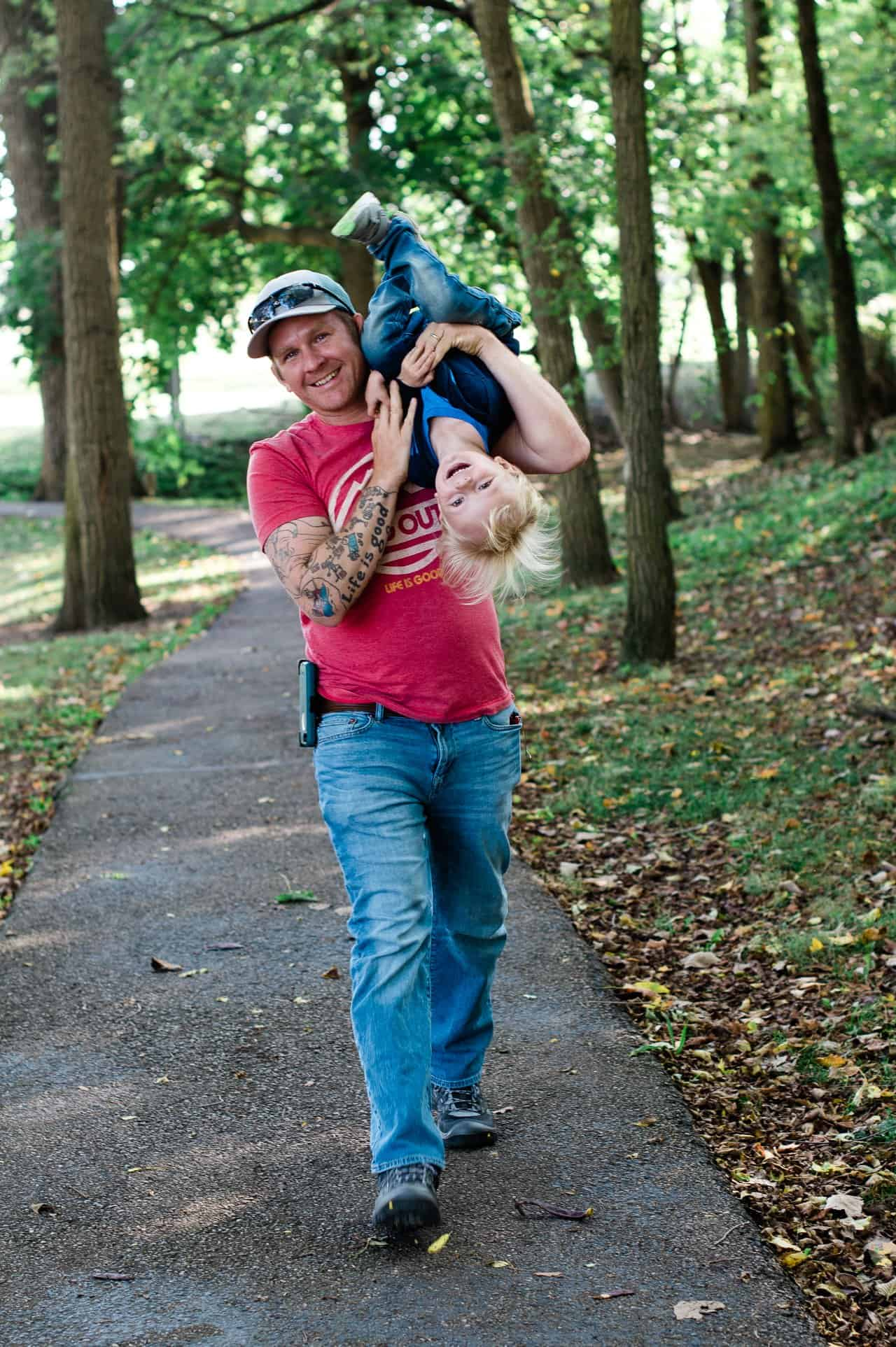 a dad holding his toddler upside down while walking