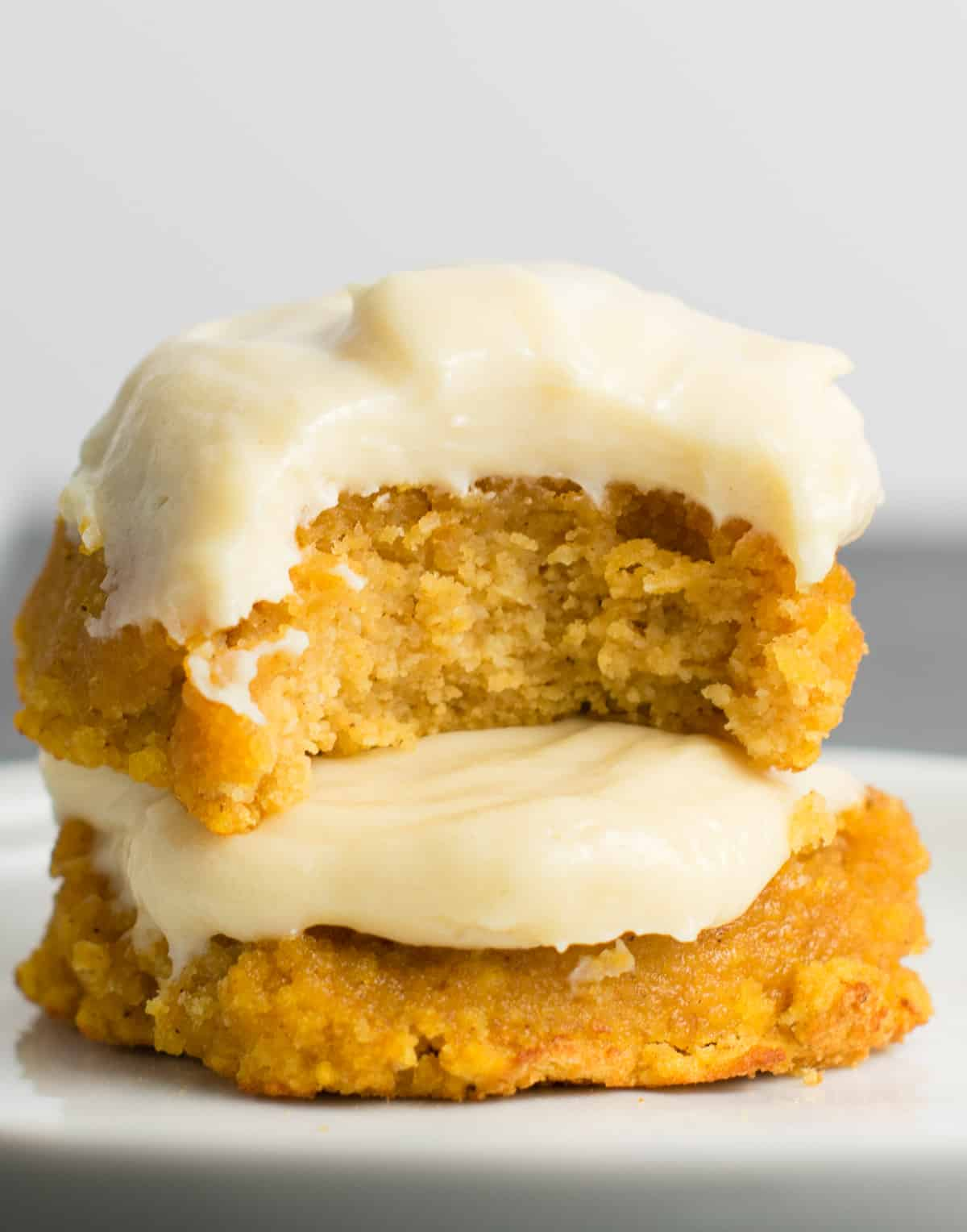 two pumpkin cookies stacked with the top one missing a bite