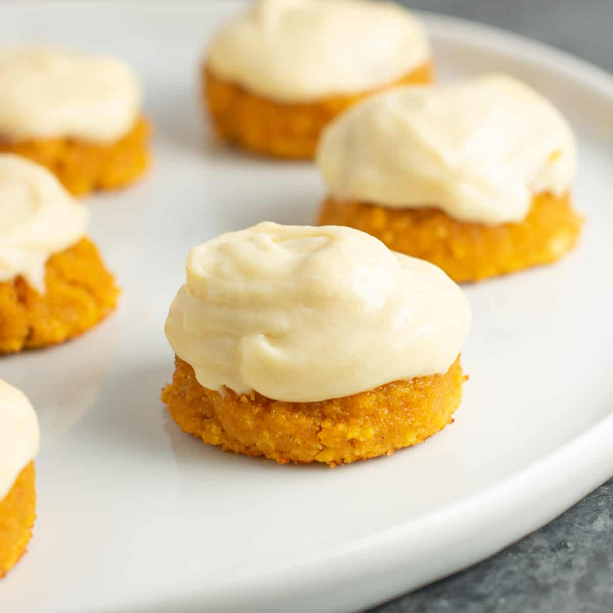 gluten free pumpkin cookies with cream cheese frosting on a plate