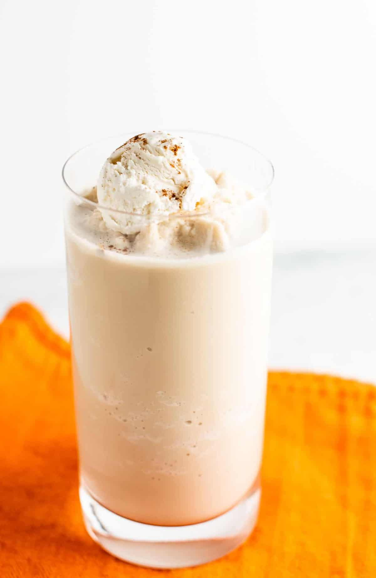 pumpkin spice frozen coffee in a clear glass on an orange napkin