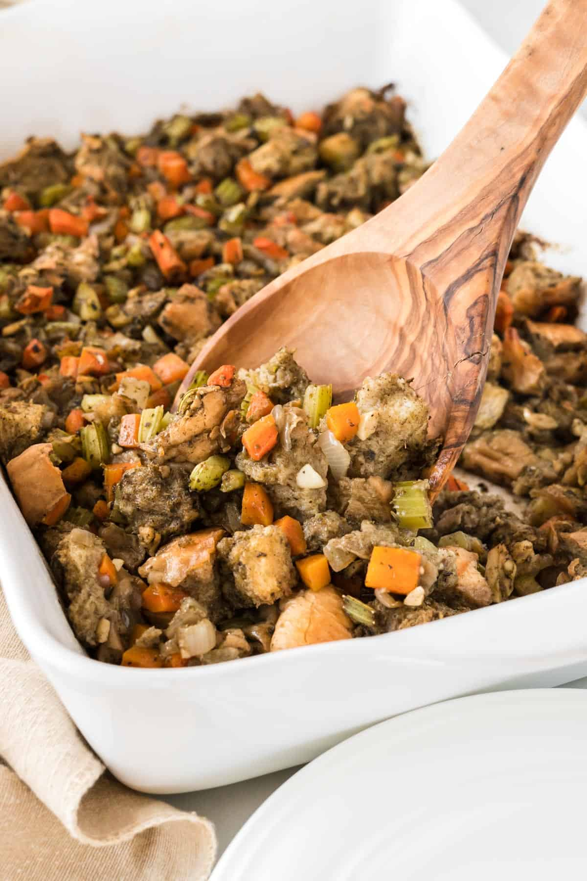 wooden spoon taking a scoop of stuffing