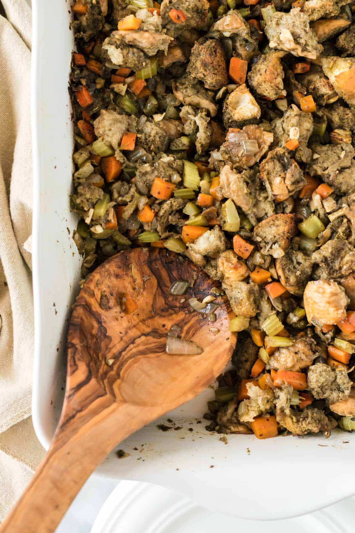 wooden spoon in a dish of vegan stuffing
