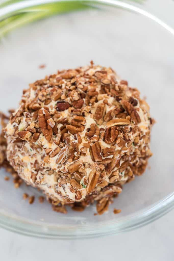 cheese ball being rolled in pecans in a bowl