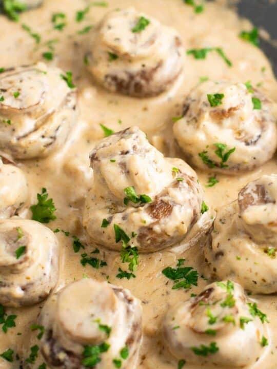 portobello mushrooms in cream sauce on a skillet sprinkled with fresh parsley