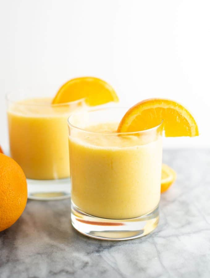 orange smoothie in a clear glass with a slice of orange on the rim