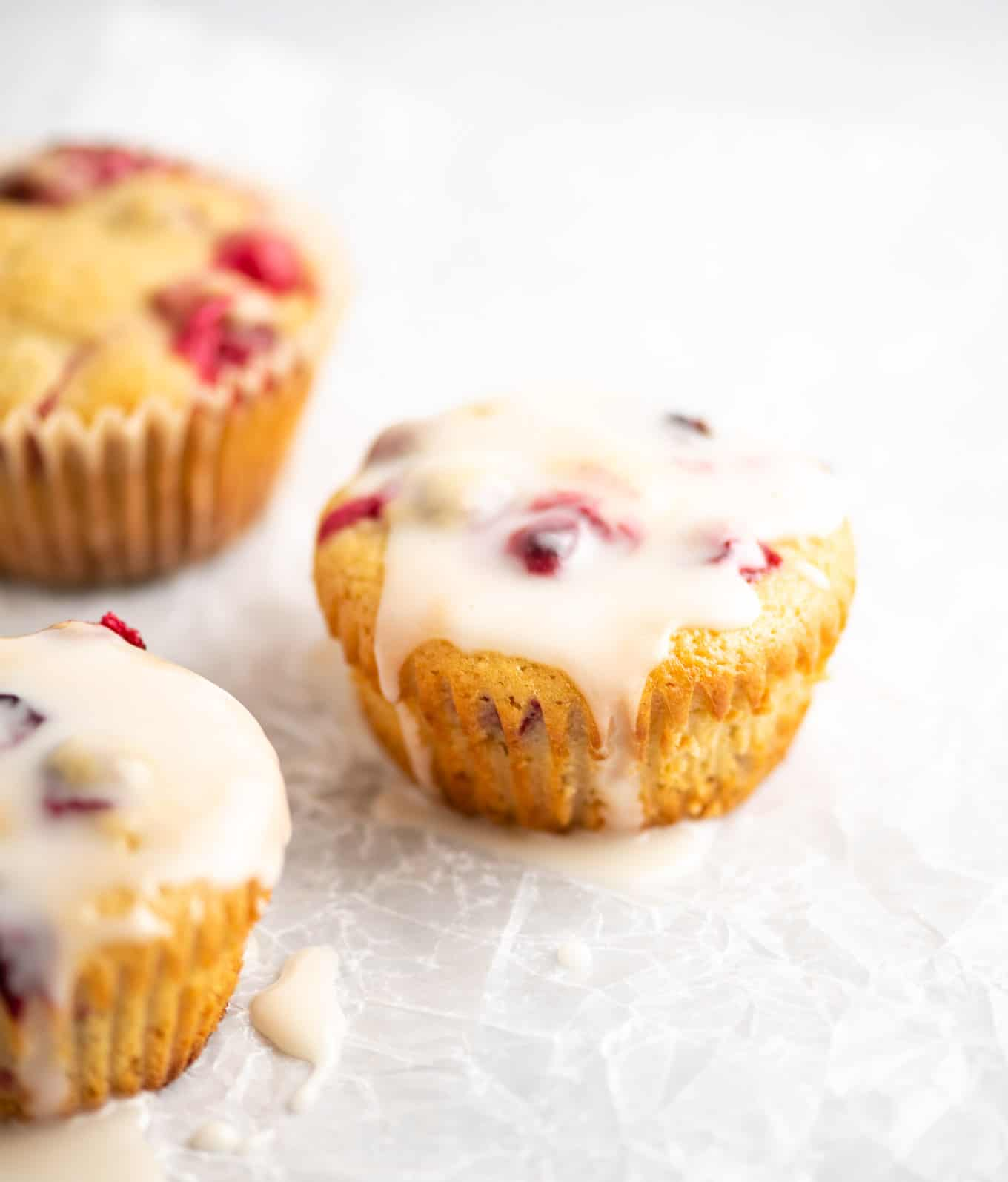 three lemon cranberry muffins on wax paper