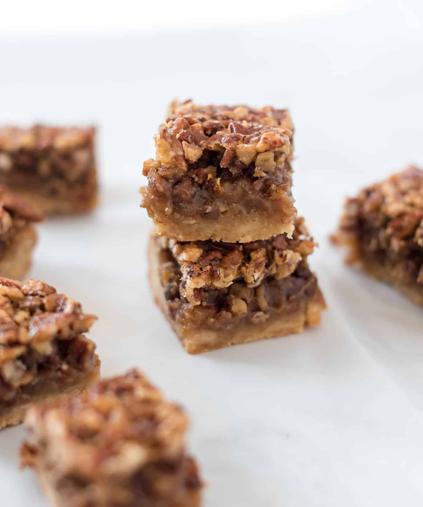two pecan pie bars stacked with bars around them