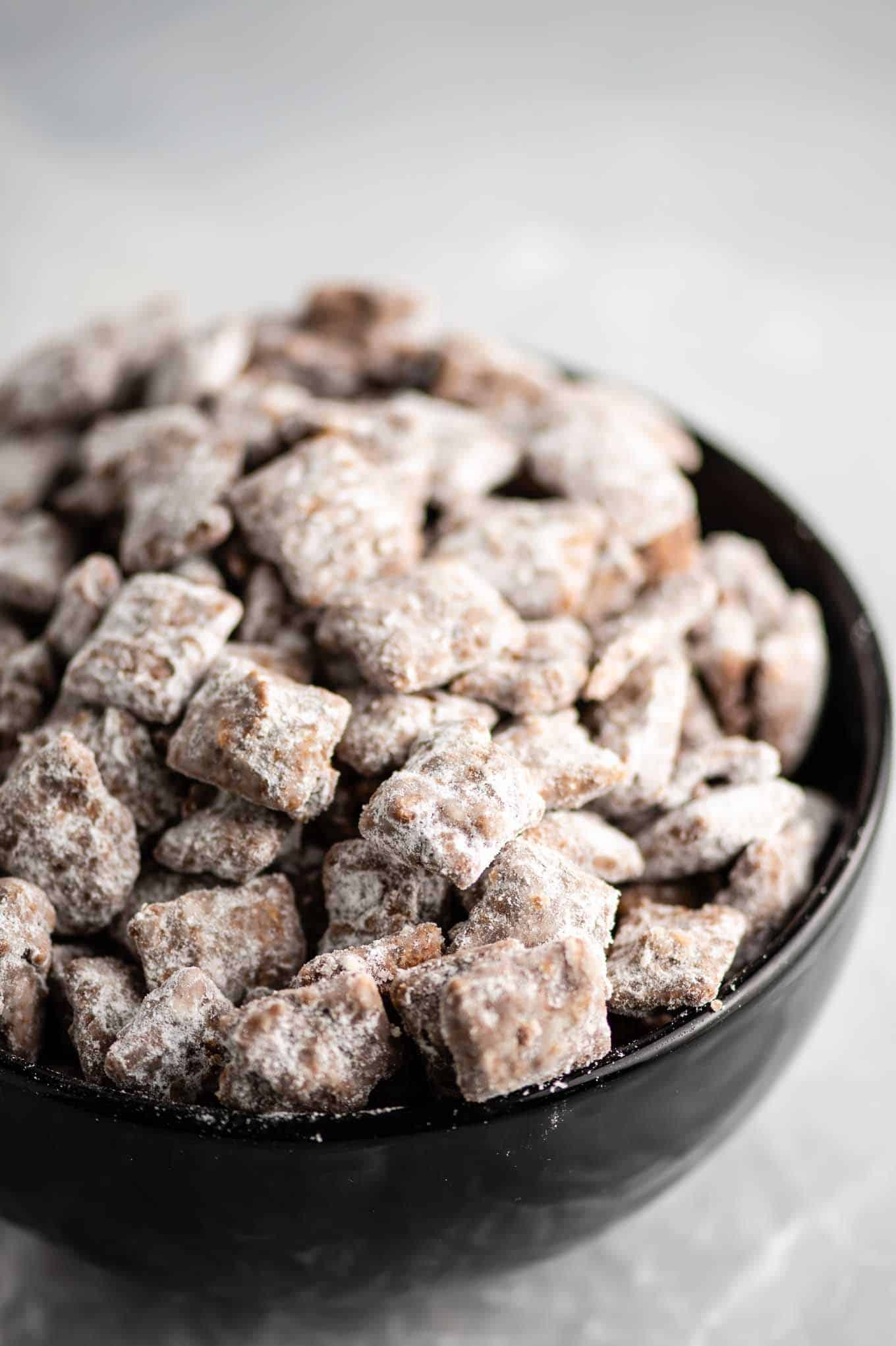 christmas puppy chow in a black bowl