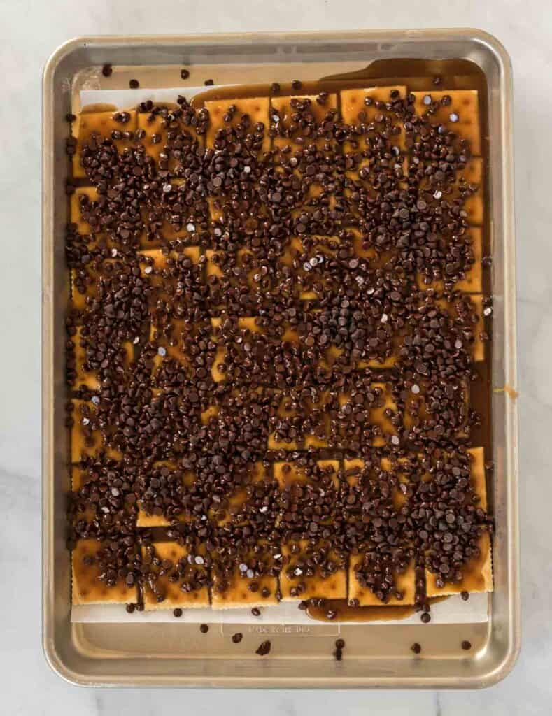 saltines on a baking sheet covered with toffee and chocolate chips