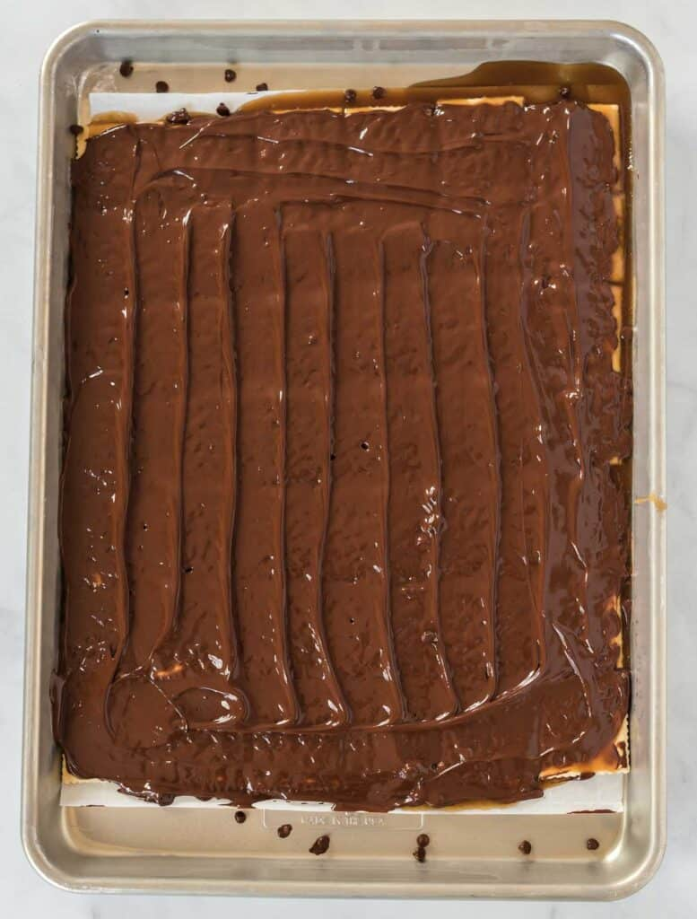 melted chocolate chips spread out over the saltine crackers on a baking sheet