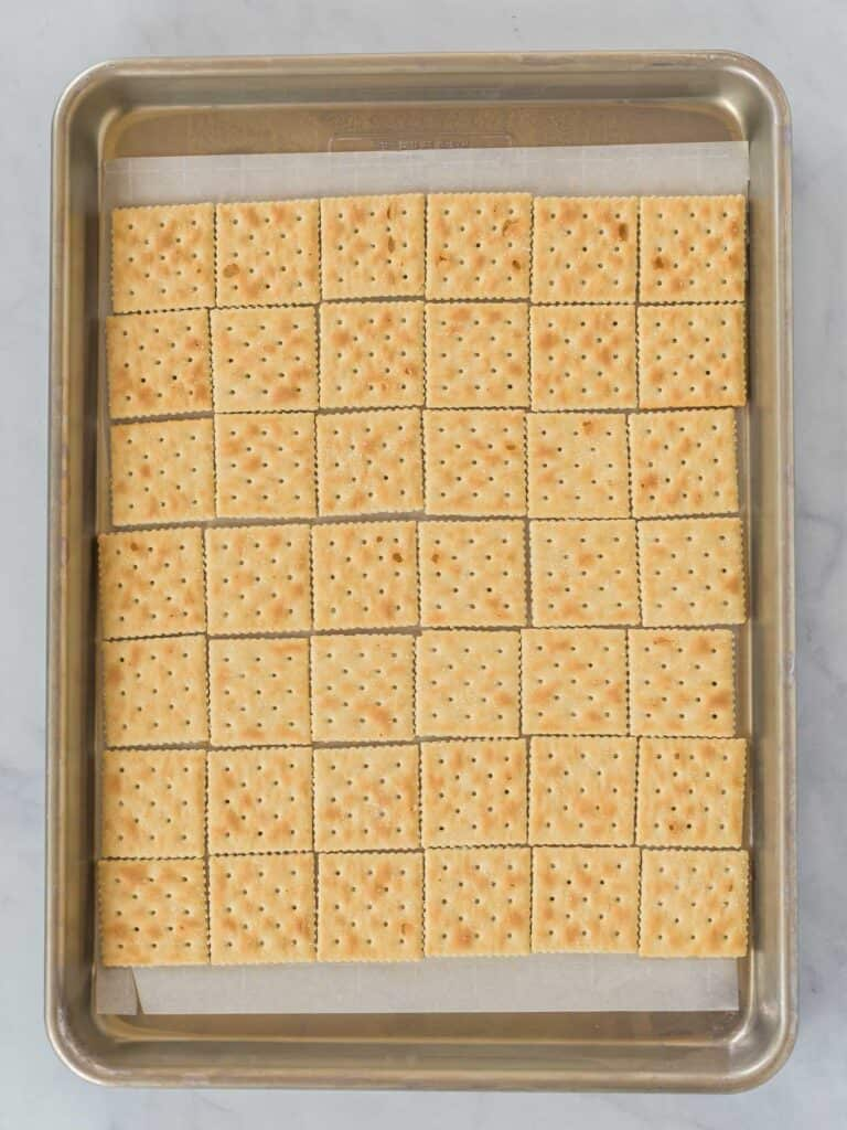 a sleeve of saltine crackers lined up in rows on a baking sheet