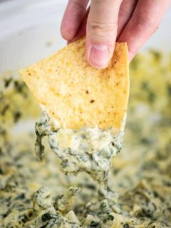 a chipped being dipped in spinach artichoke dip
