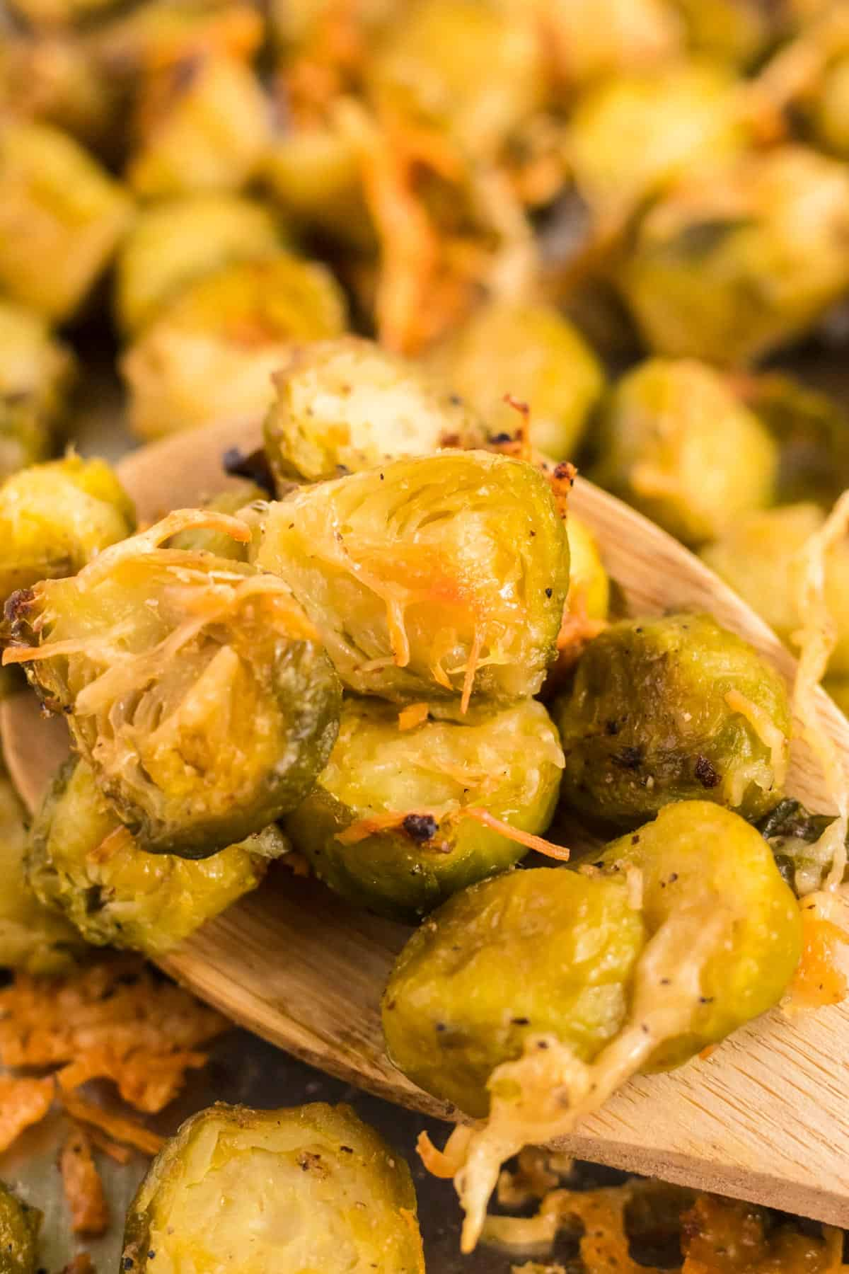 wooden spoon taking a serving of roasted brussels sprouts from the baking sheet