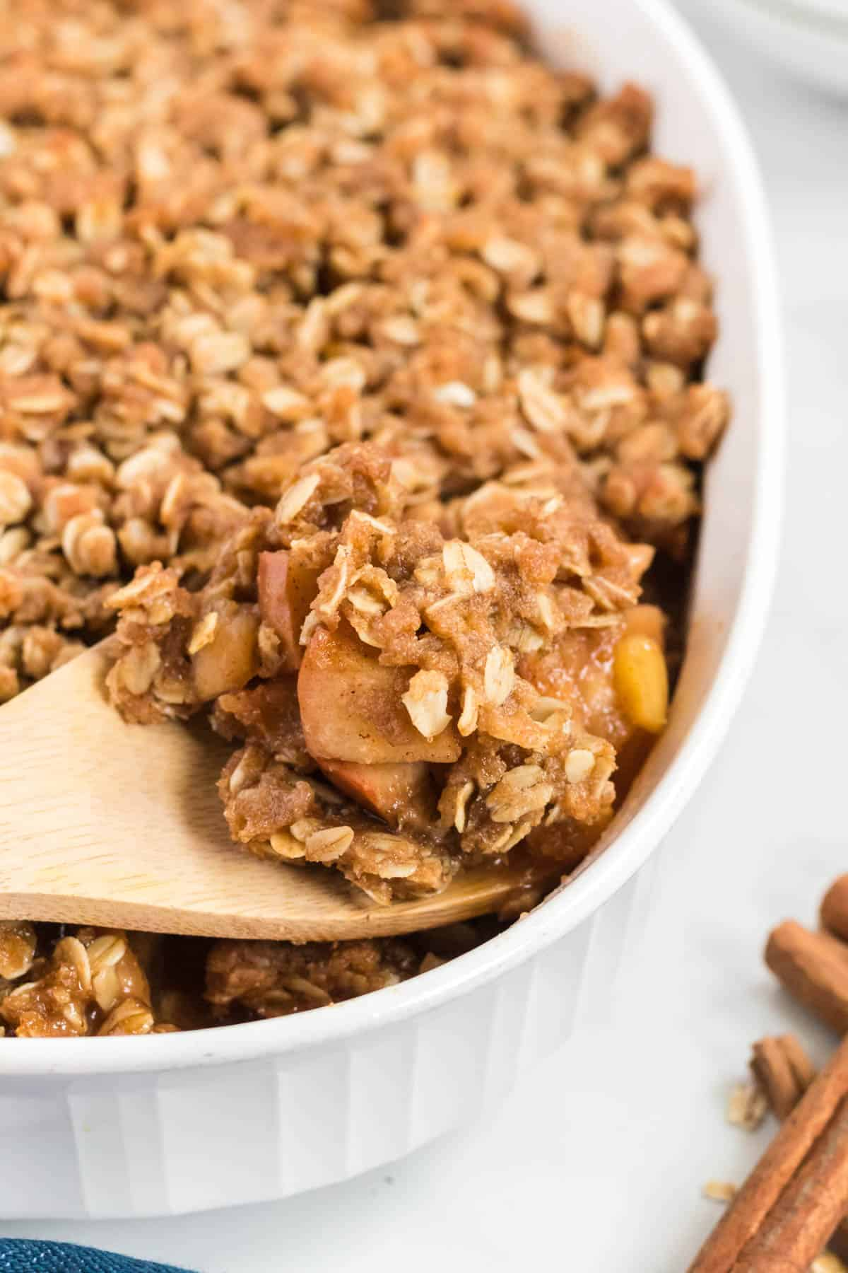 a wooden spoon scooping apple crisp from the pan