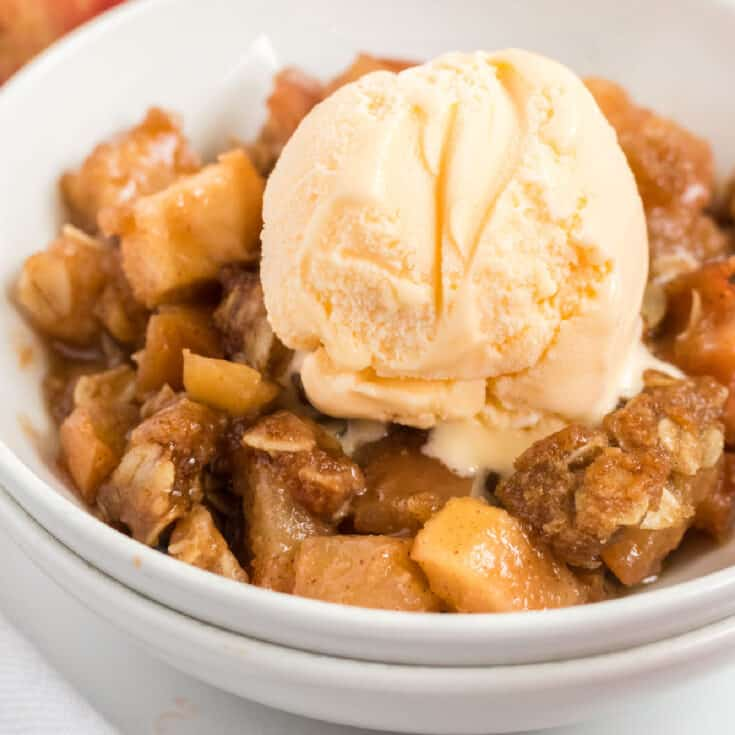 vegan apple crisp in a bowl topped with a scoop of ice cream