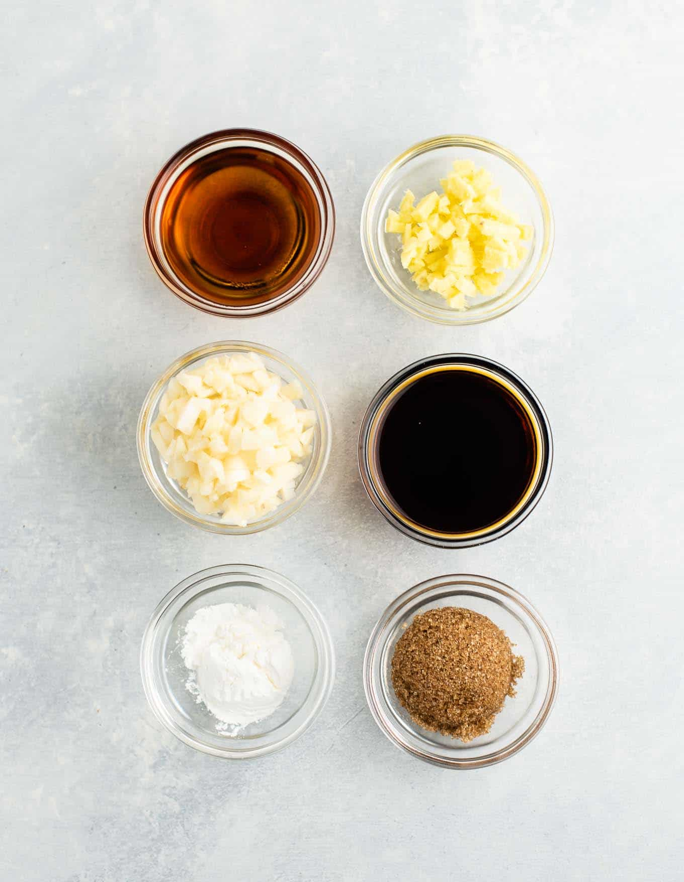6 small bowls with sesame oil, ginger, garlic, soy sauce, cornstarch, and brown sugar