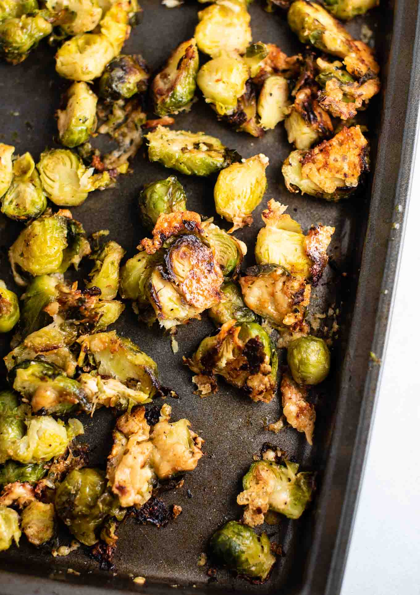 roasted frozen brussel sprouts on a black baking sheet from an overhead view