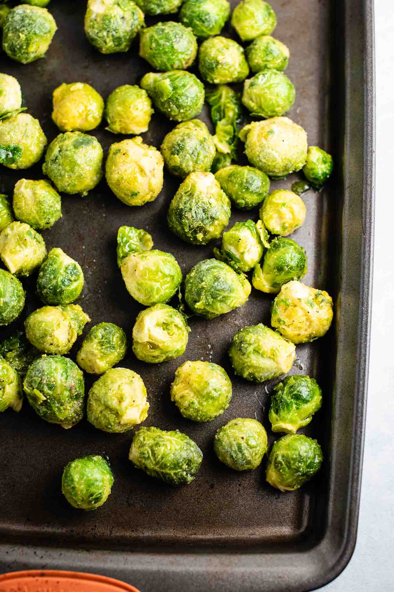 whole frozen brussels sprouts on a baking sheet before roasting