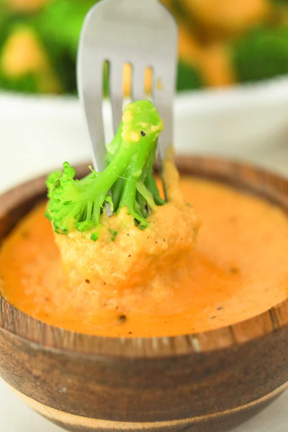 a fork dipping broccoli into a bowl of cheese sauce