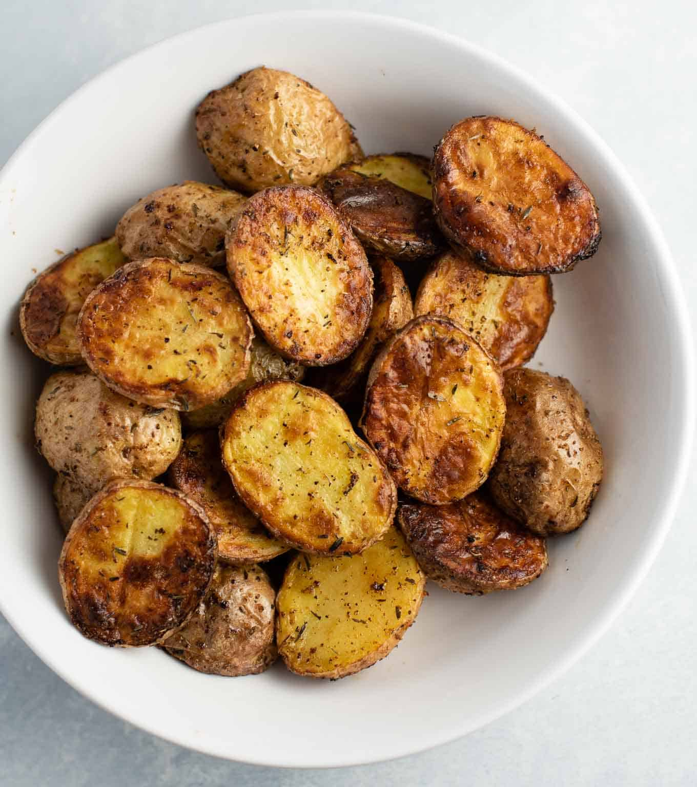 roasted potatoes in a white bowl from an overhead view