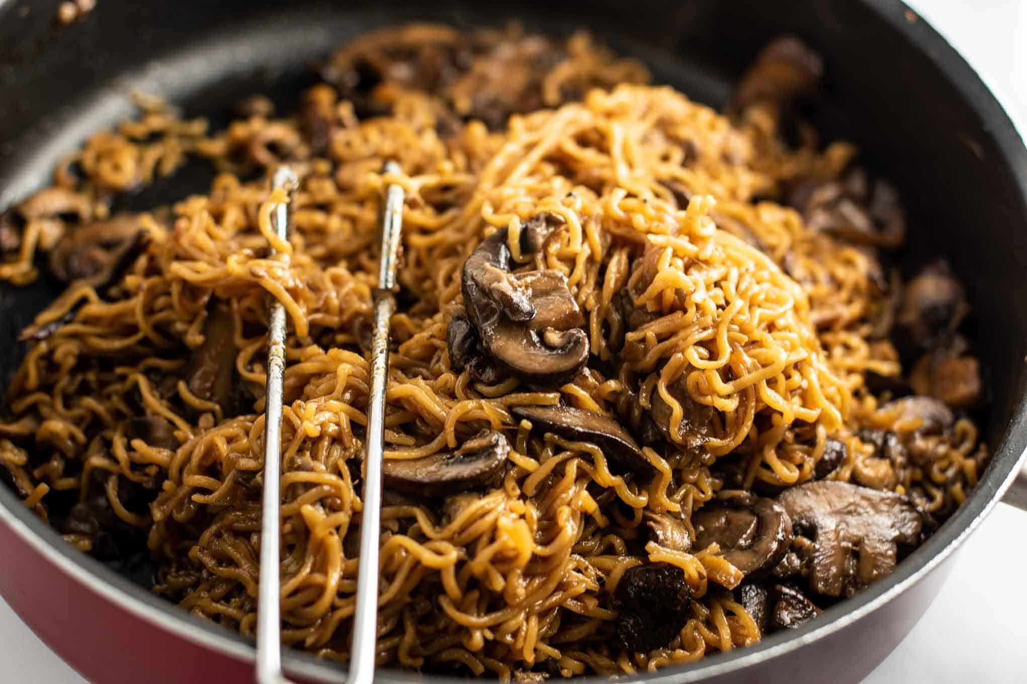 ramen noodles with mushrooms in a red jumbo cooker pan