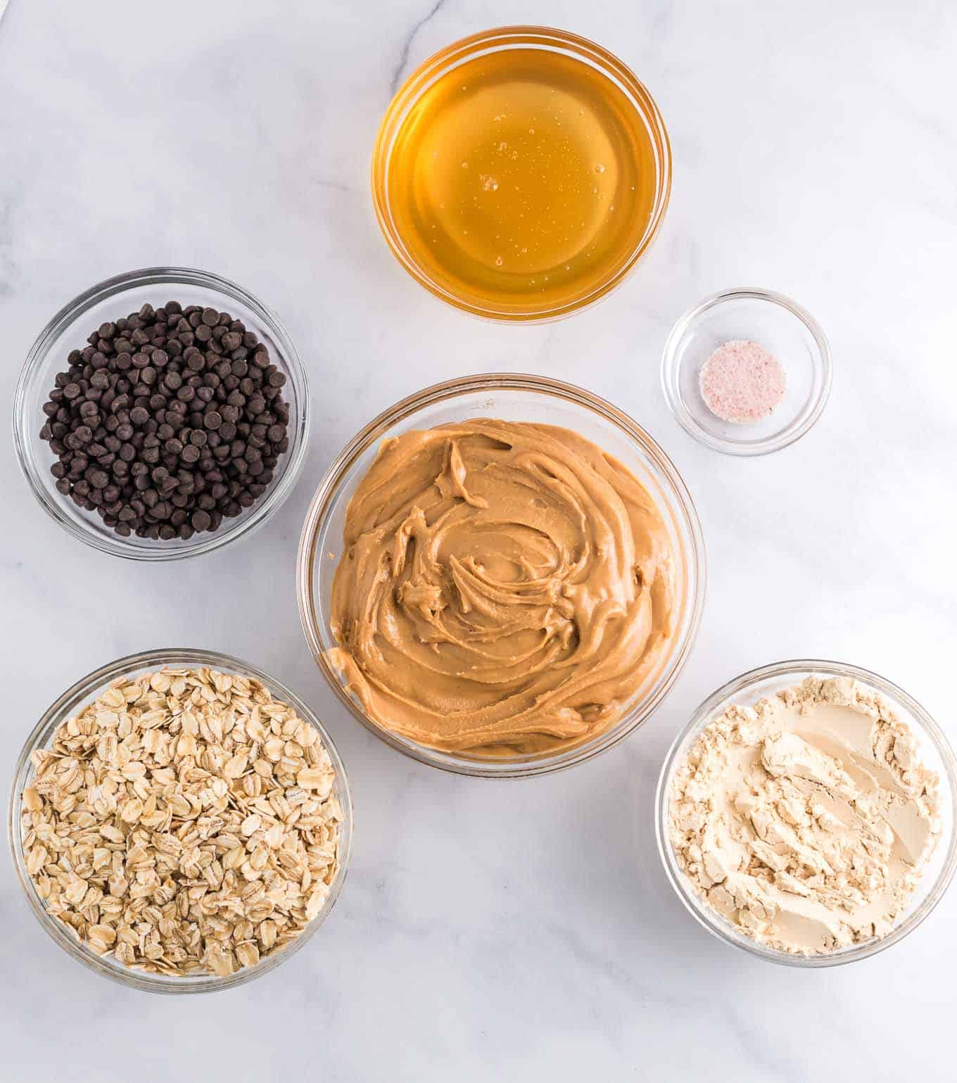 ingredients overhead picture - peanut butter, protein powder, salt, oats, honey, and mini chocolate chips