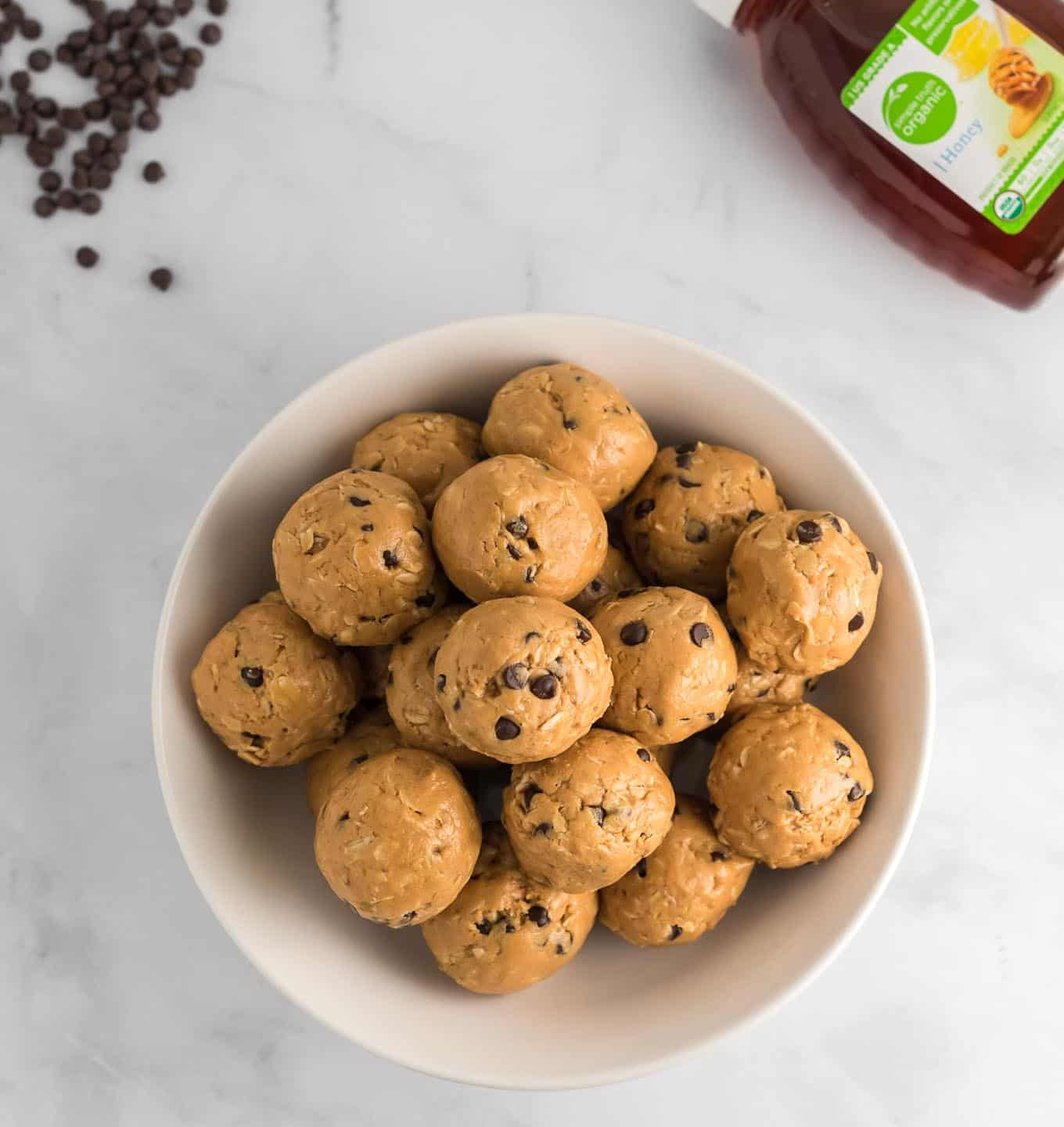 energy balls with honey and chocolate chips in the corner of the photo