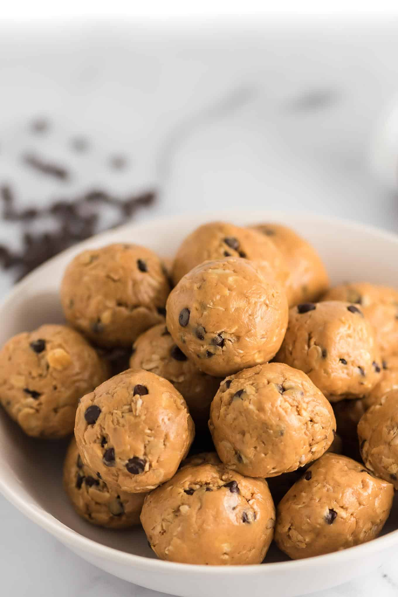 energy balls in a bowl from the side with chocolate chips in the background