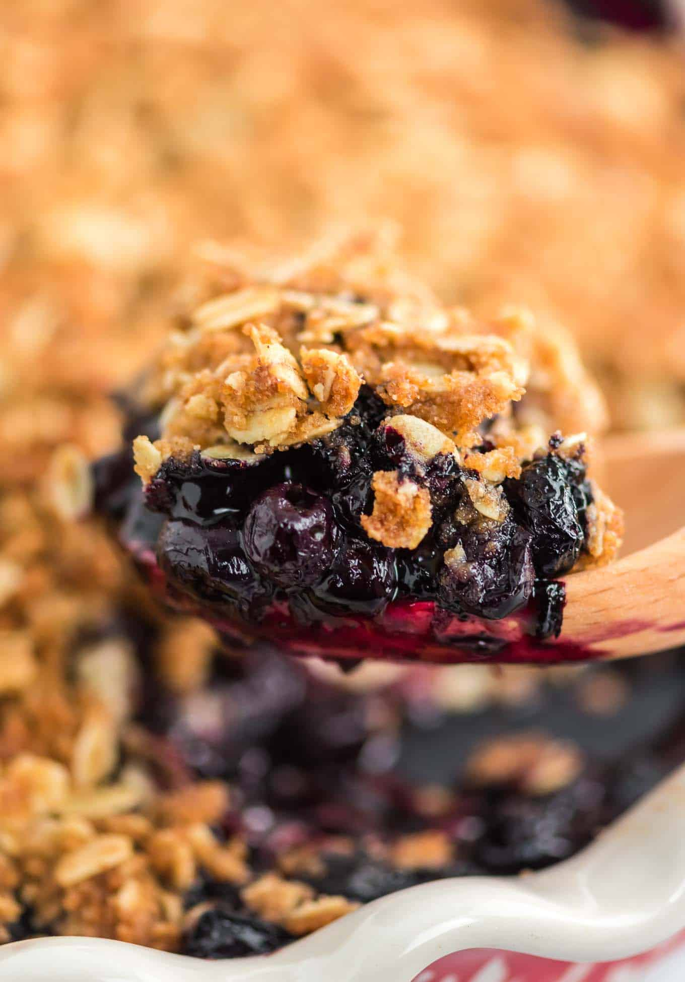 a wooden spoon taking a scoop of blueberry crisp