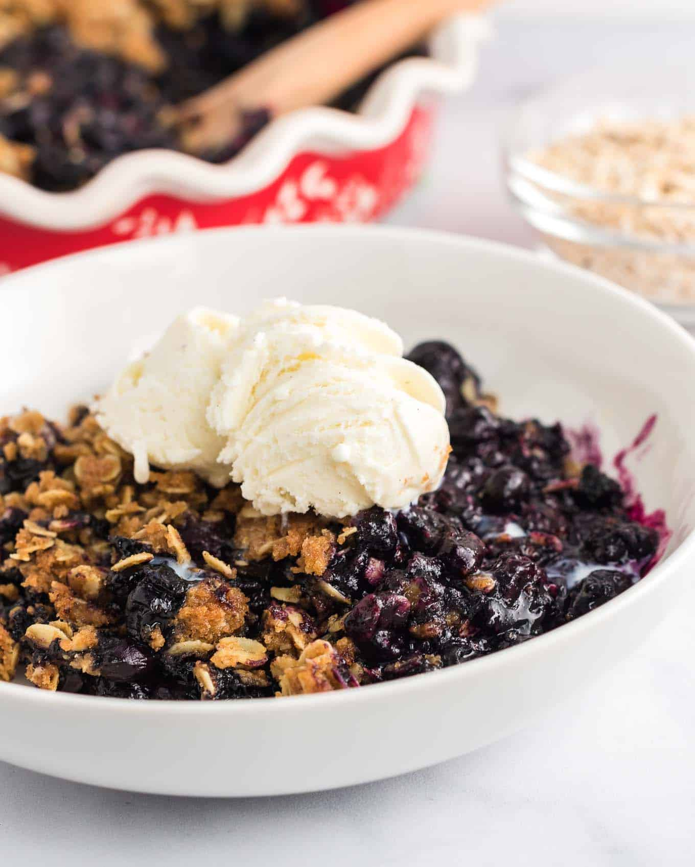 blueberry crisp in a white bowl with two scoops of ice cream on top